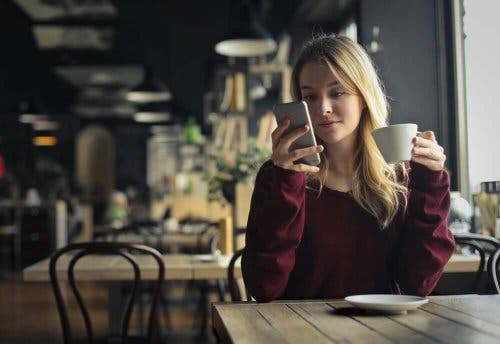Kvinde på café sidder med sin telefon