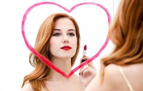 Kvinde maler hjerte på spejl med læbestift