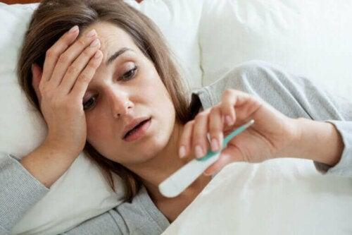 Kvinde i seng med termometer i hånden har Q-feber