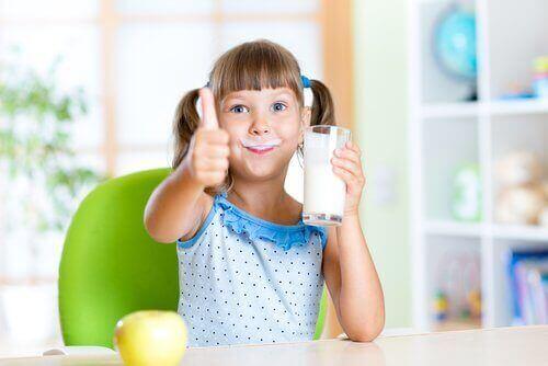 Pige med mælkeskæg og et glas mælk i hånden