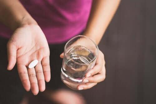 Kvinde med pille og vand i hænderne