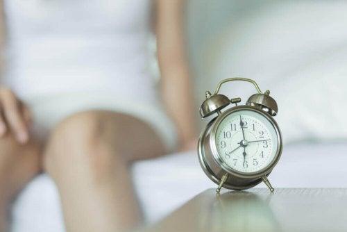 Kvinde med vækkeur tænker over, hvad der påvirker søvnen