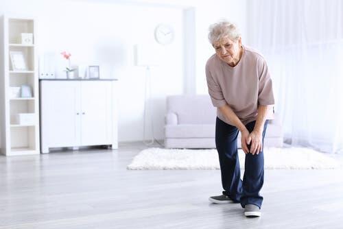 Ældre kvinde tager sig til knæ
