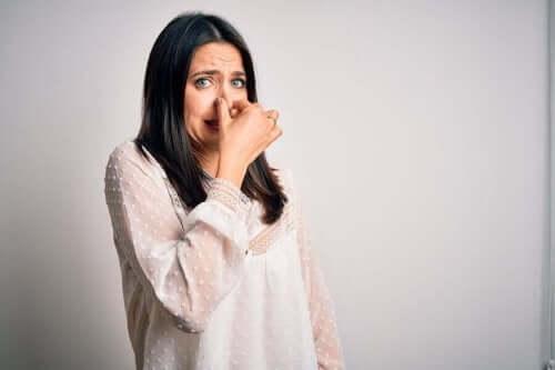 Kvinde holder sig for næse som symbol for, når folk ikke går i bad