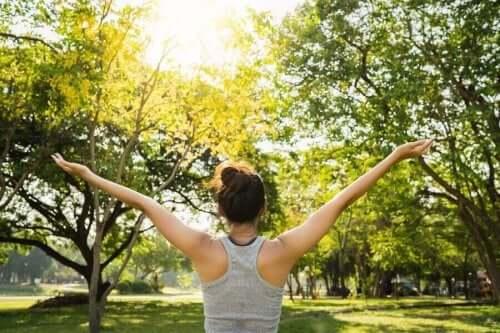 Jordforbindelse er en praksis, der foreskriver at øge din forbindelse til naturen for at fremme dit velbefindende, som denne kvinde i park udøver