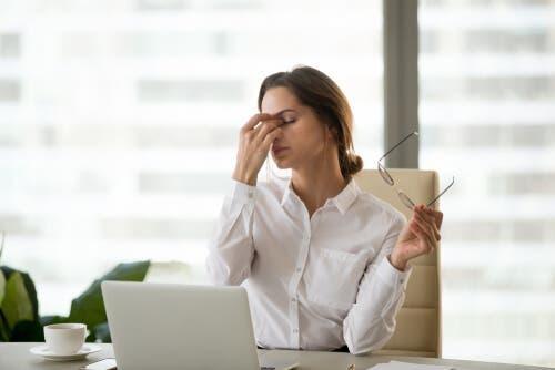 Kvinde ved computer tager sig til øjne