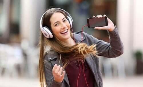 Smilende kvinde lytter til musik i høretelefoner