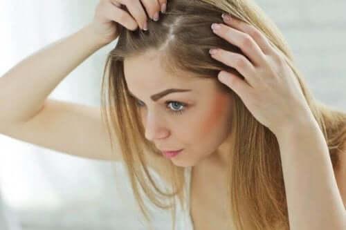 Kvinde tjekker hovedbund for grå hår