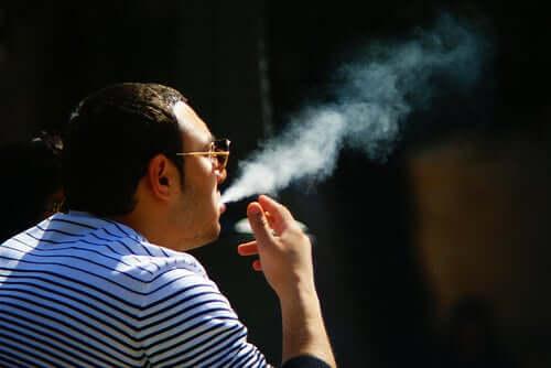 Mand sidder og ryger, selvom tobak påvirker huden