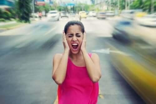 Kvinde på vej holder sig for ørerne, da støj påvirker humøret