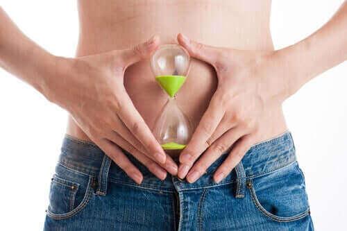 Timeglas foran kvindes mave