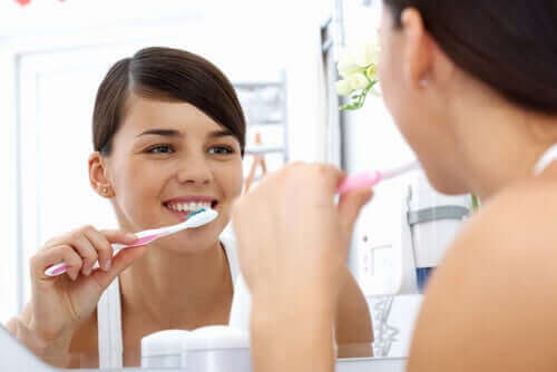 Kvinde børster tænder for at undgå bakterier i munden