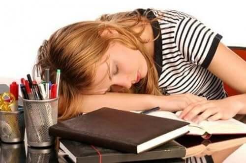 Det er almindeligt, at personer med højt niveau af ferritin føler sig træt og svag, som denne pige, der sover på skrivebord