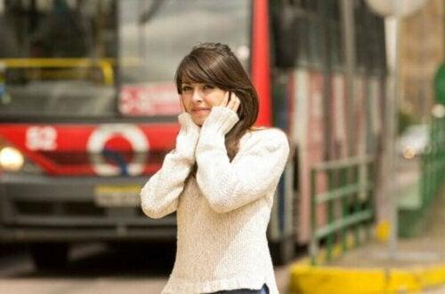 Kvinde ved støjende køretøjer holder sig for ørerne
