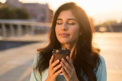 Kvinde nyder kaffe udenfor som en del af at forbedre sit følelsemsæssige helbred