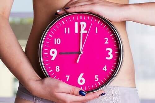 Kvinde med ur symboliserer, når kvinders menstruation synkroniserer