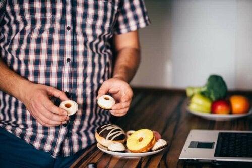 Mand med kager oplever konsekvenserne af at overspise