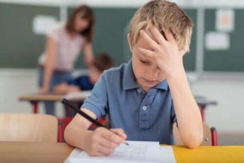 Dreng i klasseværelse tager sig til hoved grundet migræne hos børn