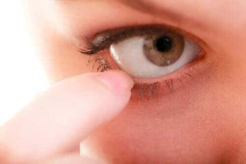 Kvinde sætter finger i sit øje