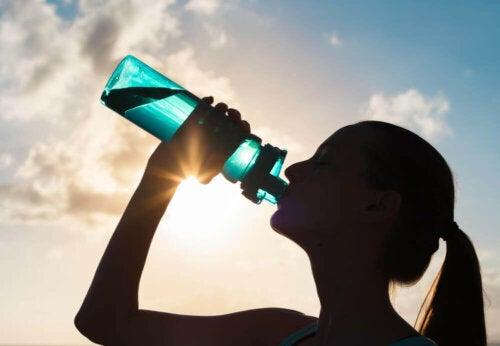 Kvinde drikker vand for at undgå ubalance i elektrolytter