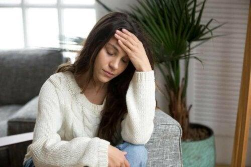 Kvinde med hovedpine tager sig til hoved grundet mangel på tid til at hvile