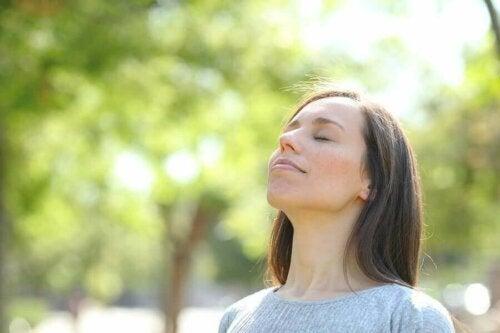 Kvinde nyder frisk luft i naturen