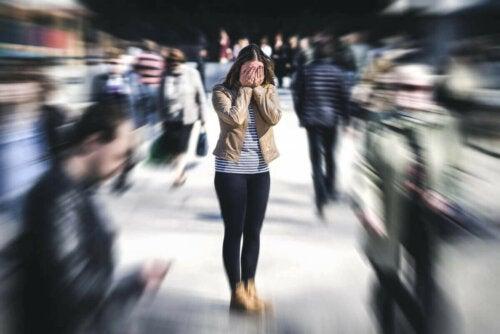 Panisk kvinde i menneskemængde af plaget af agorafobi