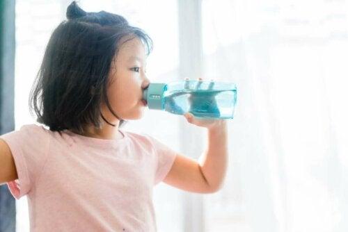 Pige drikker vand af drikkedunk