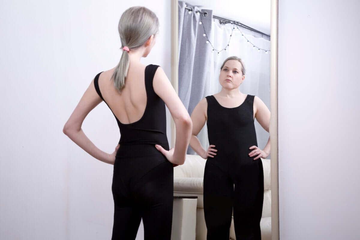 Slank kvinde ser sig selv som overvægtig i spejl grundet sadomasochistisk anoreksi