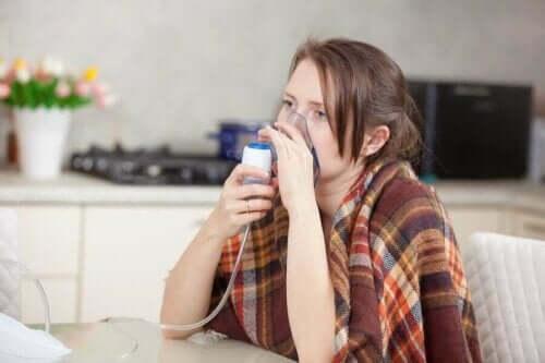 Kvinde med kold lungebetændelse anvender maske til at trække vejret