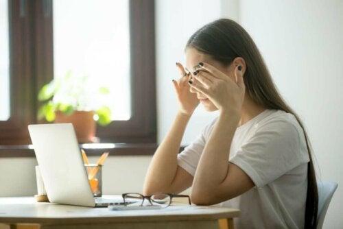 Kvinde med hovedpine ved computer