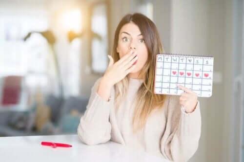 Overrasket kvinde med kalender over menstruationscyklus