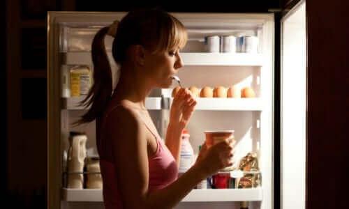 Kvinde spiser fra åbent køleskab om aftenen