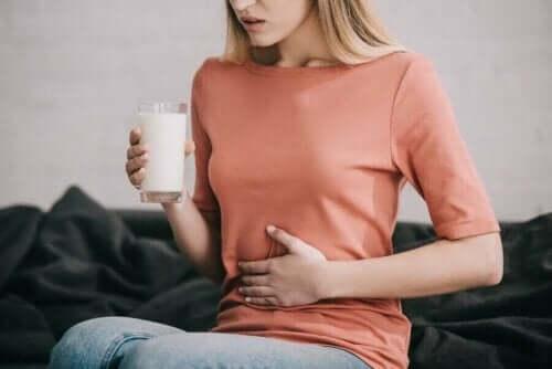 Kvinde tager sig til mave med et glas mælk i hånden