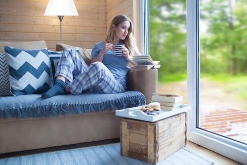 Kvinde nyder bog i sofa