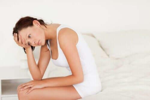 Utilpas kvinde sidder på seng