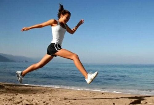 Kvinde motionerer på strand for at forebygge knogletab