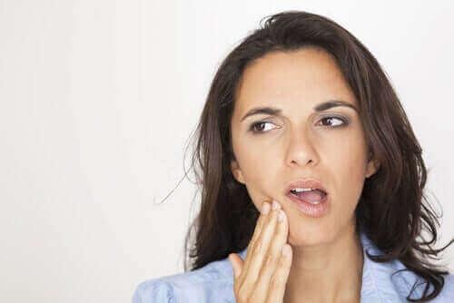 Kvinde med sensitive tænder tager sig til mund