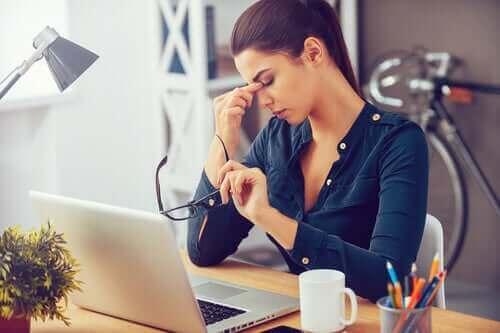 Kvinde ved skrivebord har hovedpine grundet daglig stress