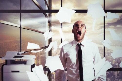 Stresset mand kaster med papirer