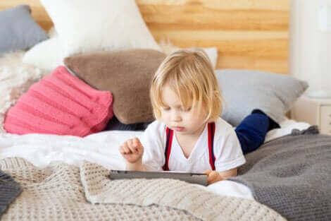 Barn med ipad i seng illustrerer for meget skærmtid