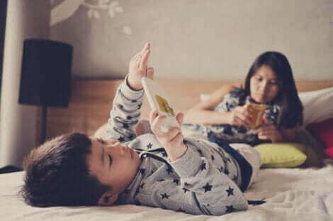 Børn med smarttelefoner i seng illustrerer for meget skærmtid