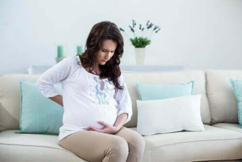 Gravid kvinde tager sig til maven, da hun oplever underlivssmerter under graviditet