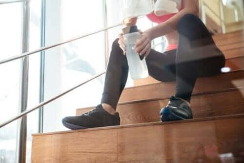 Kvinde sidder på trappe med vand efter træning