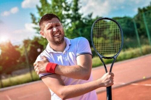 Mand, der dyrker tennis, tager sig til skulderen