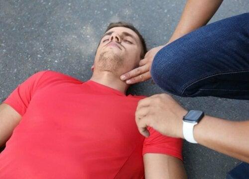 Mand, der ligger på vej, får tjekket sin puls