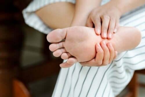 Person med plantar fasciitis har ondt i foden