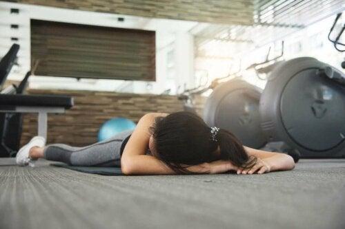 Kvinde på gulv i motionscenter illustrerer pludselige dødsfald indenfor sport
