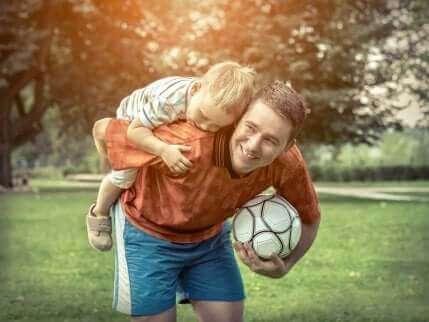 Far og søn med fodbold i park