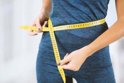 Kvinde måler omkredsen om maven